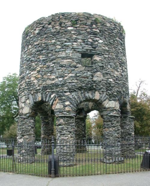 Squat round tower of grey stone over 8 arches